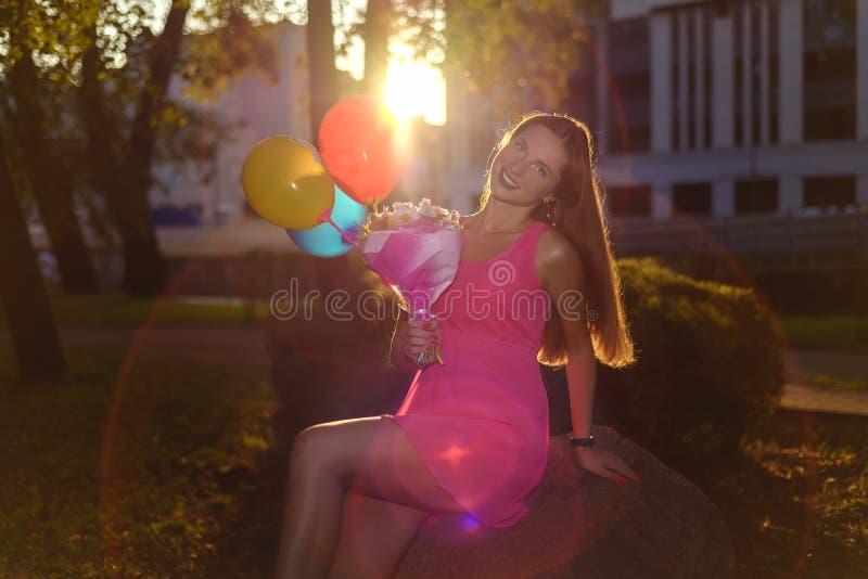 Красивая девушка с букетом цветков и воздушных шаров в розовом платье стоковое изображение rf