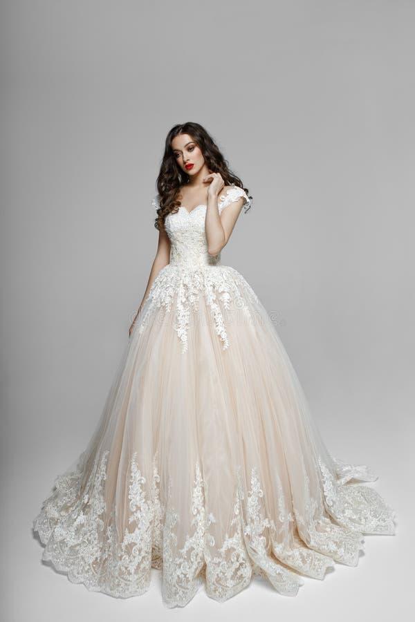 Красивая девушка с вьющиеся волосы в wendding платье, он касается его шеи с его рукой, изолированной на белой предпосылке стоковое изображение rf