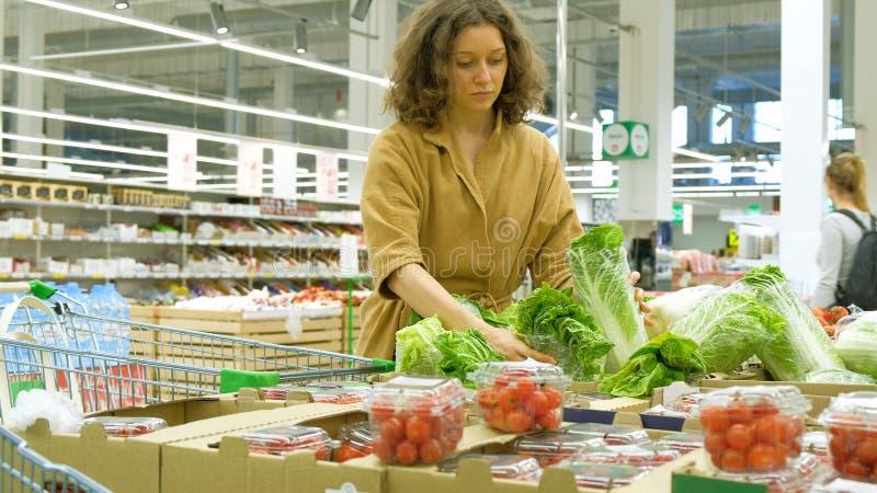 Красивая девушка с вьющиеся волосы принимает зеленый свежий салат стоковое изображение