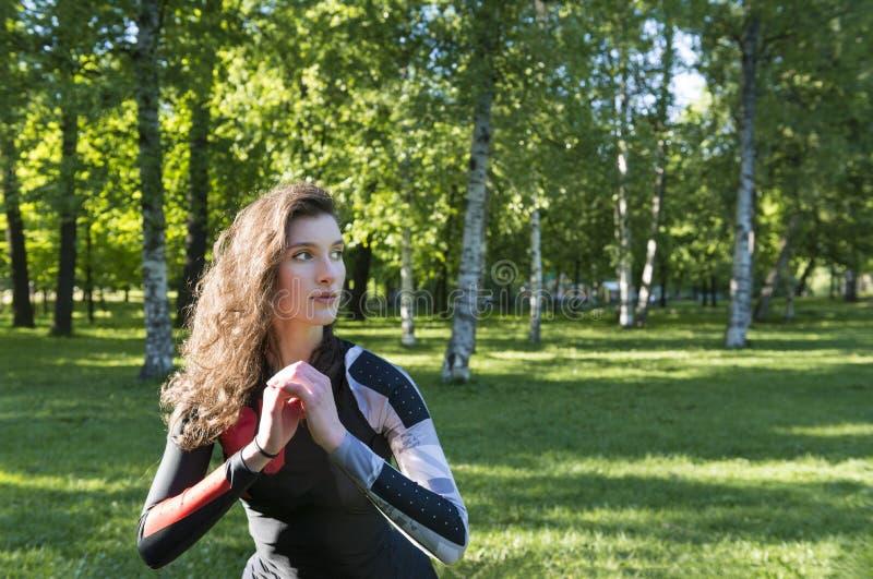 Красивая девушка с длинными волнистыми волосами делая спорт в парке на фоне растительности стоковое фото rf