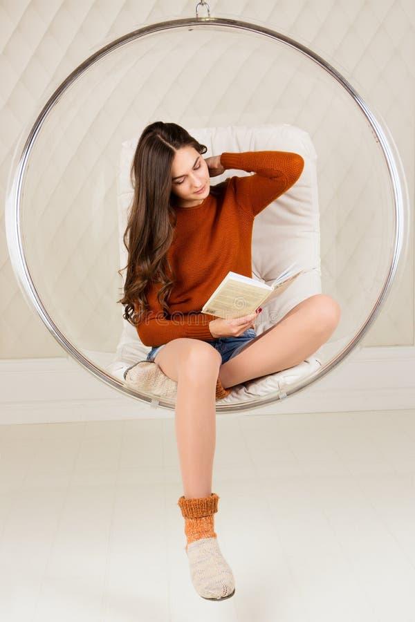 Красивая девушка с длинными волосами книга чтения, в привесном стуле Домашний интерьер, тонизированное изображение, обрабатывать  стоковое фото rf