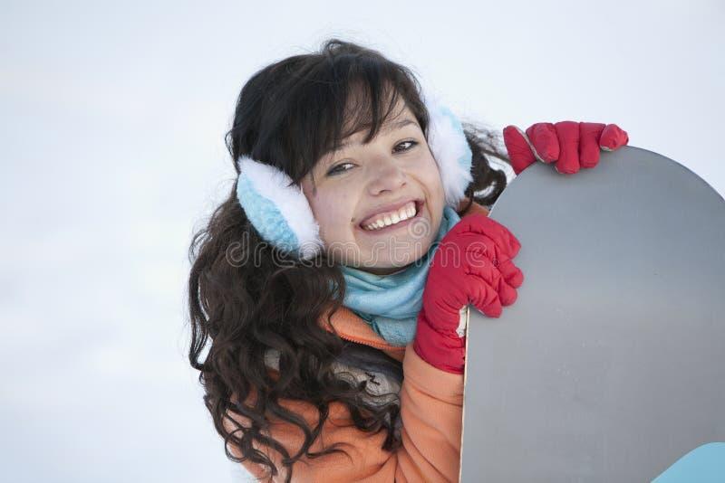 Красивая девушка с длинными волосами, со сноубордом стоковое изображение