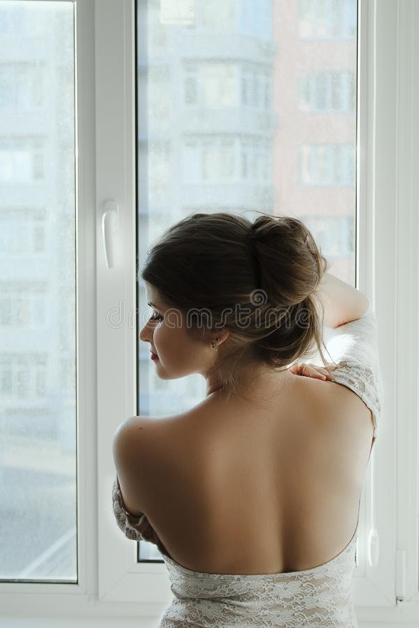 Красивая девушка с длинными каштановыми волосами в белом положении платья на окне от задней части стоковые фотографии rf