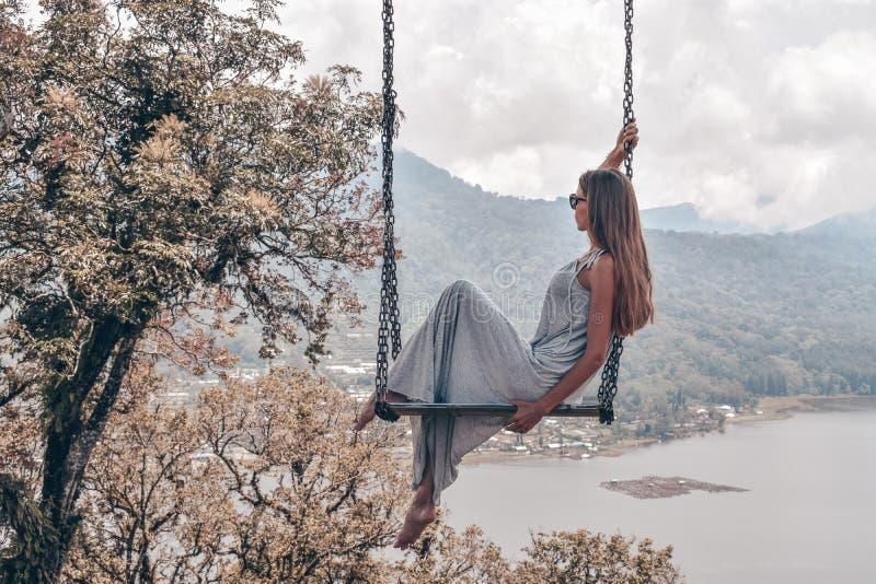 Красивая девушка с длинными темными волосами в элегантный серый представлять платья стоковые фотографии rf