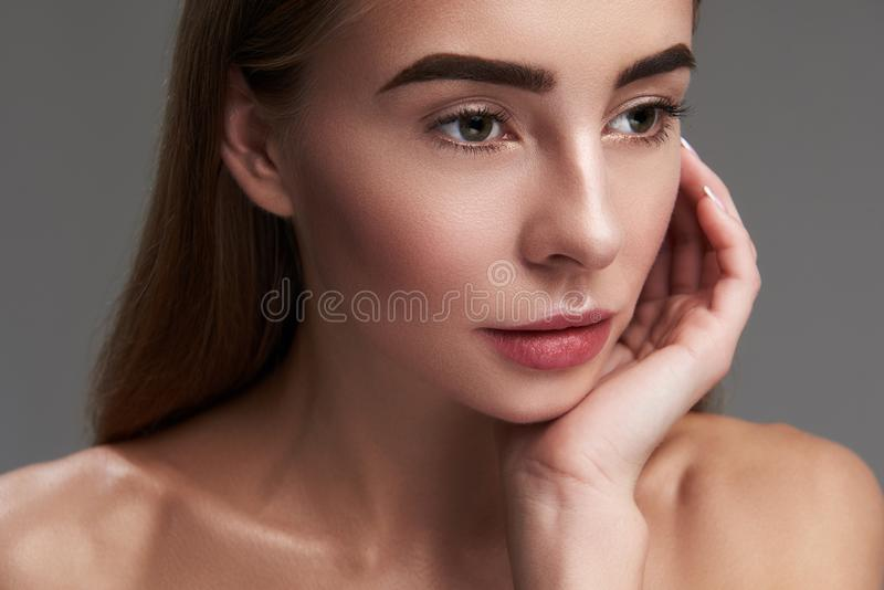 Красивая девушка с идеальной кожей представляя против серой предпосылки стоковые изображения rf