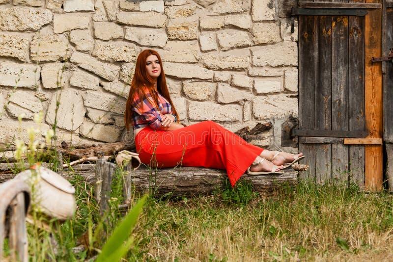 Красивая девушка с оранжевыми волосами в рубашке шотландки и красно- пинке sk стоковое фото