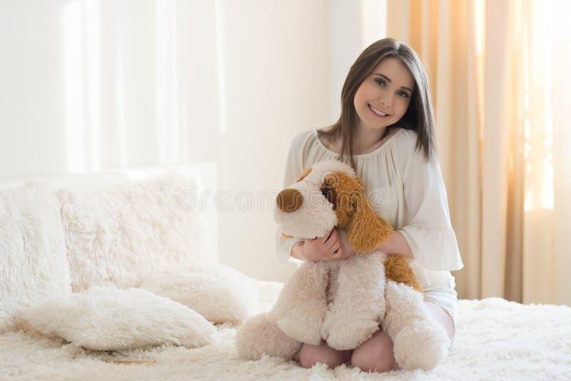 Красивая девушка с собакой плюша на кровати стоковая фотография rf