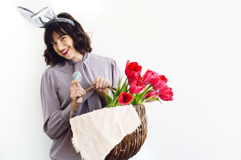Красивая девушка с ушами зайчика усмехаясь и держа пасхальное яйцо и тюльпаны в деревенской корзине на белой предпосылке внутри п стоковые фото