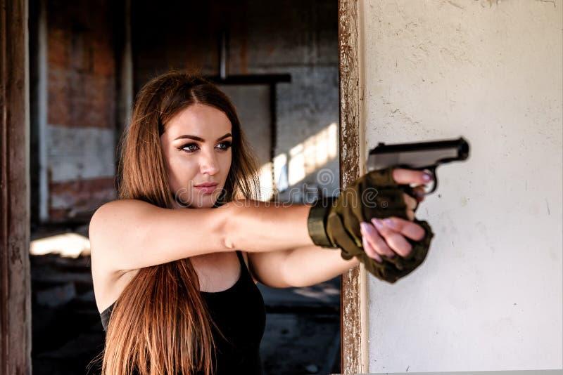 Красивая девушка с черным оружием стоковое фото rf