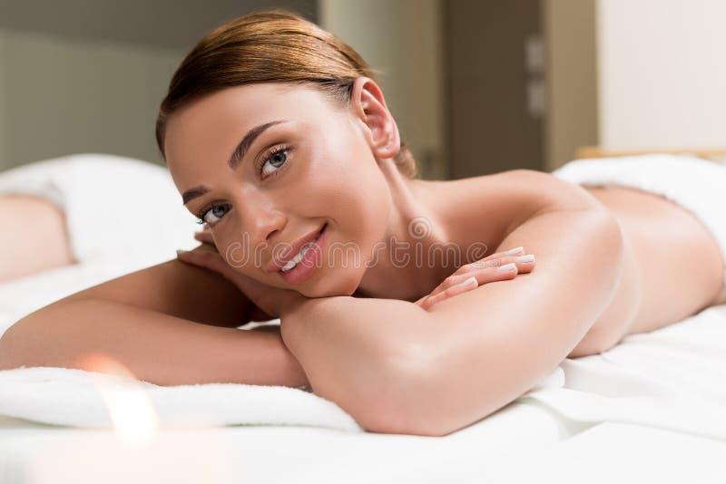 красивая девушка усмехаясь на камере пока лежащ на таблице массажа стоковые изображения rf