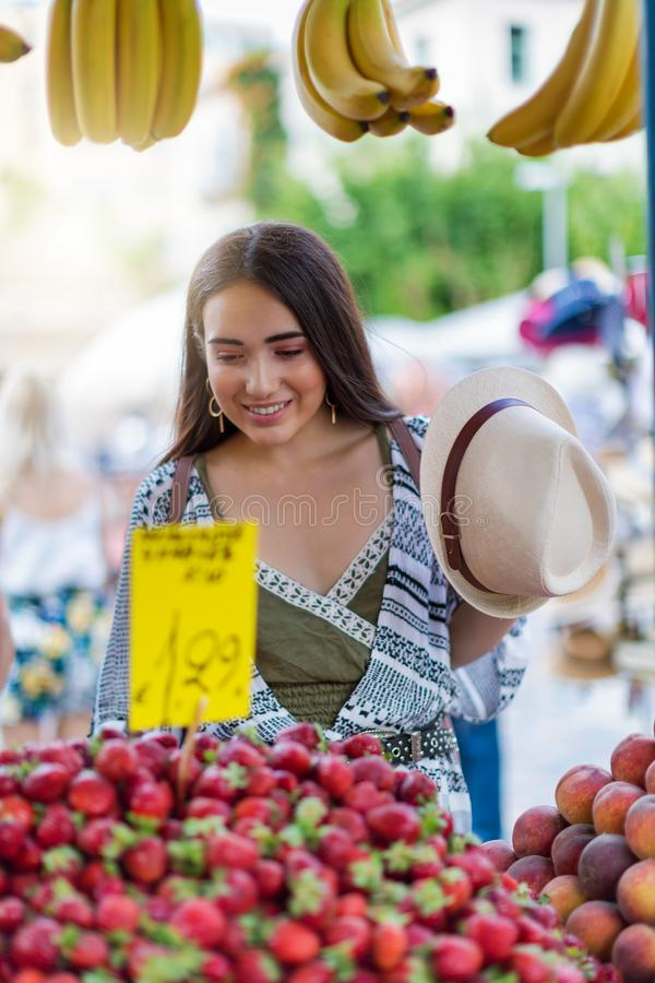 Красивая девушка ходит по магазинам на свежих фруктах рынка стоковое изображение