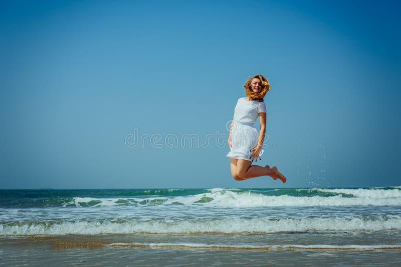 Красивая девушка Joyfull скача на пляж E стоковое изображение