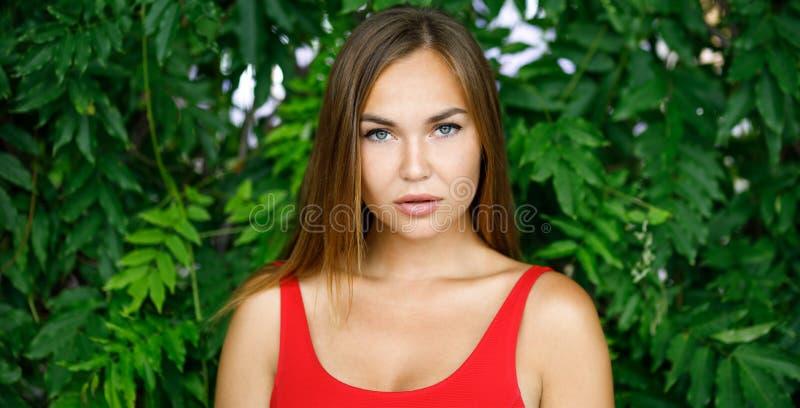 Красивая девушка outdoors в красном платье стоковая фотография rf