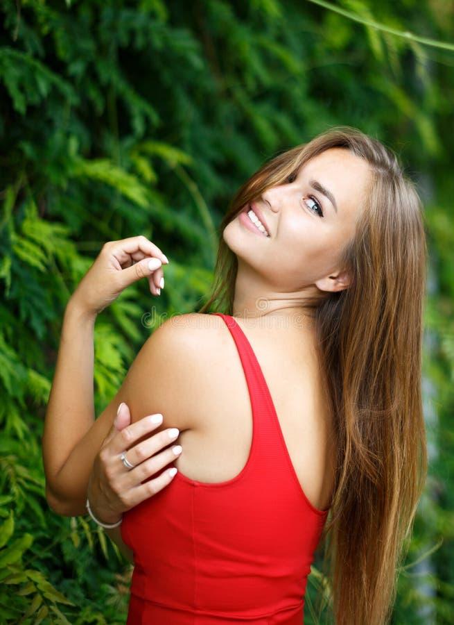 Красивая девушка outdoors в красном платье стоковое изображение