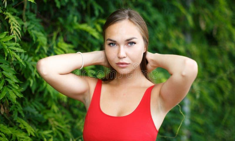 Красивая девушка outdoors в красном платье стоковое фото