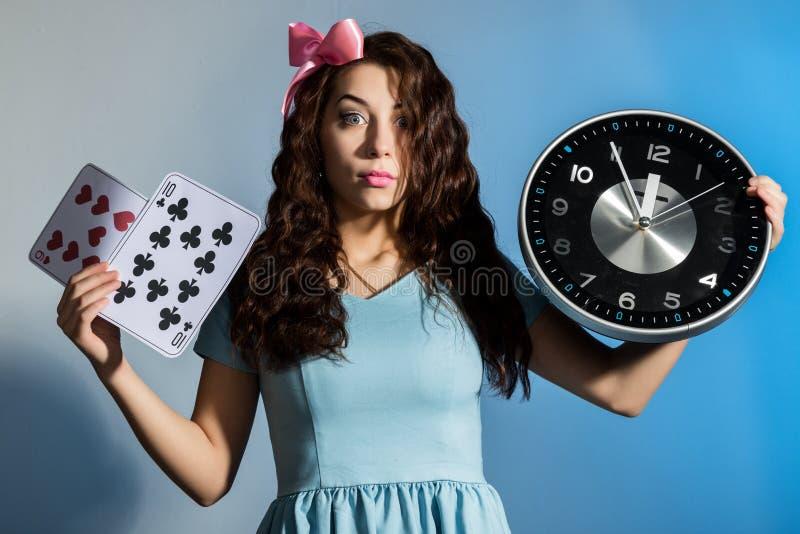 Красивая девушка pinup в голубом платье держа большие часы на голубой предпосылке стоковые фото