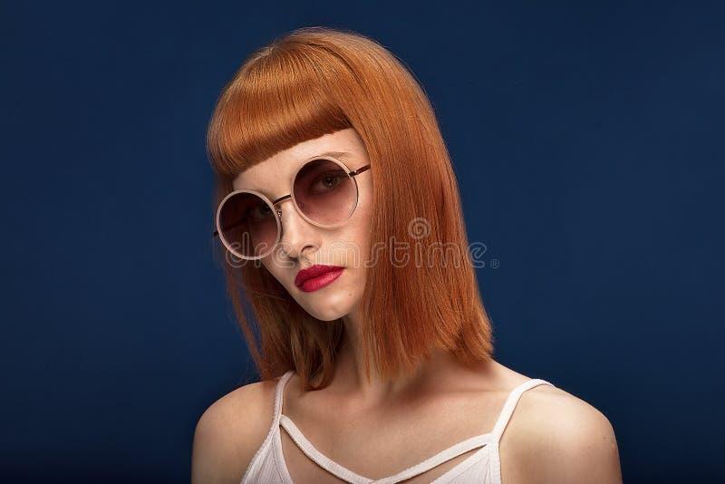 Красивая девушка redhead в солнечных очках на голубой предпосылке стоковая фотография rf