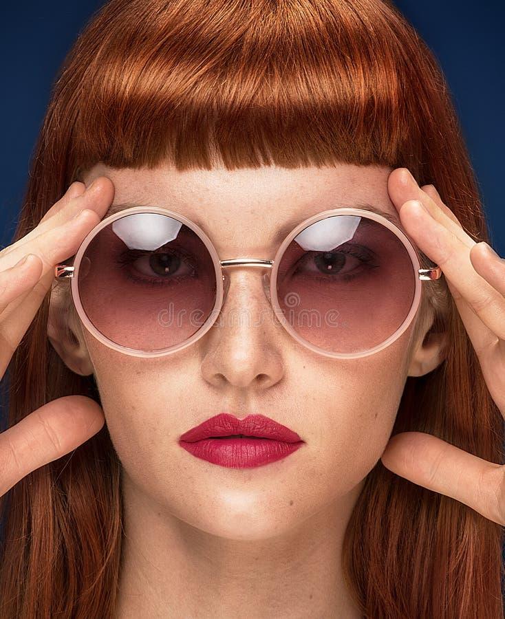 Красивая девушка redhead в солнечных очках на голубой предпосылке стоковые фотографии rf
