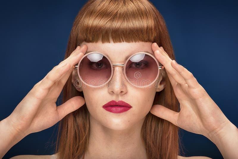 Красивая девушка redhead в солнечных очках на голубой предпосылке стоковое изображение