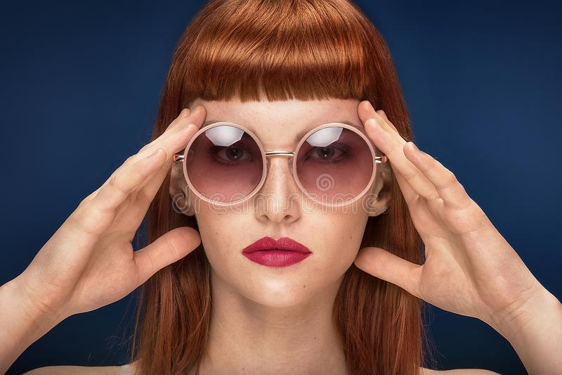 Красивая девушка redhead в солнечных очках на голубой предпосылке стоковая фотография