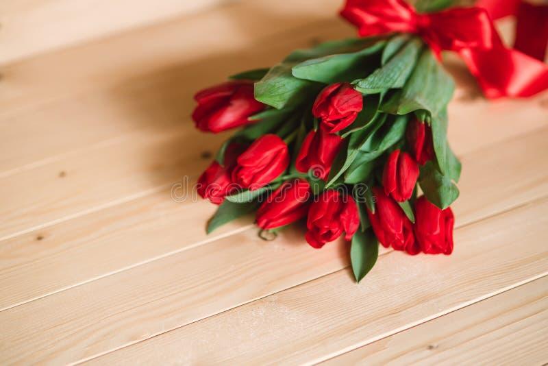 Красивая деревенская предпосылка с красными тюльпанами Красочная карточка на день матерей, день рождения, международный день 8-ое стоковые фотографии rf