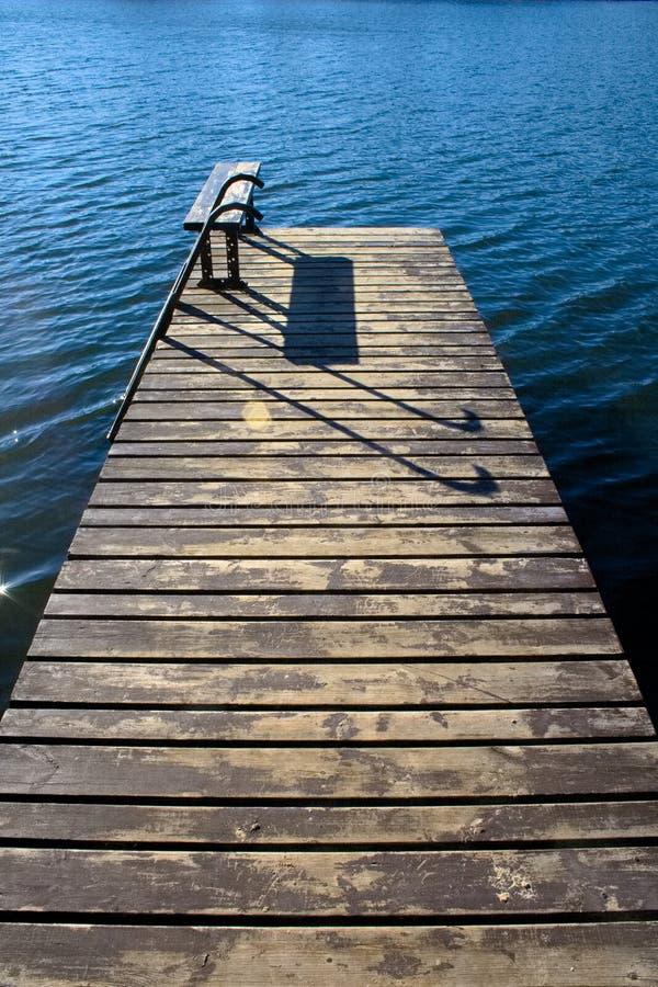 Красивая деревянная пристань с стендом и солнцем отразила на затишье и открытом море стоковое изображение