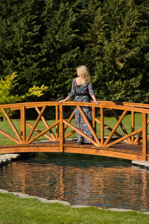 Красивая длинная с волосами белокурая стойка женщины на деревянном мосте над искусственным прудом, в естественном окружает, зелен стоковое изображение