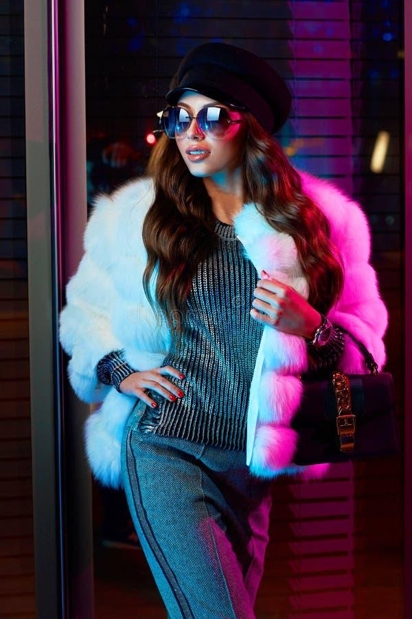 Красивая длинная с волосами женщина в крышке, солнечных очках и белом coa меха стоковые изображения