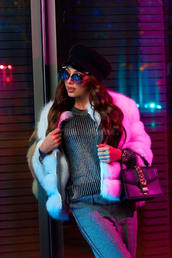 Красивая длинная с волосами женщина в крышке, солнечных очках и белом coa меха стоковые фото