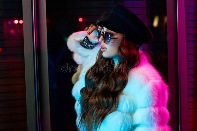 Красивая длинная с волосами женщина в крышке, солнечных очках и белом coa меха стоковые изображения rf