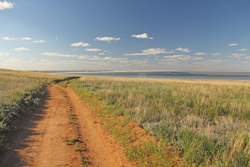 Красивая дорога в поле, идет за горизонтом голубое небо зеленого цвета травы Красивейший ландшафт лета стоковое фото