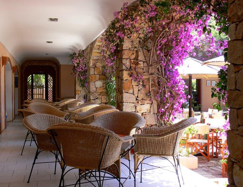 Красивая дорожка аркады с уютными плетеными стульями стоковые фото