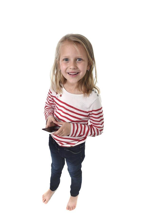 Красивая девочка с светлыми волосами и голубыми глазами используя мобильный телефон играя игру стоковые фотографии rf