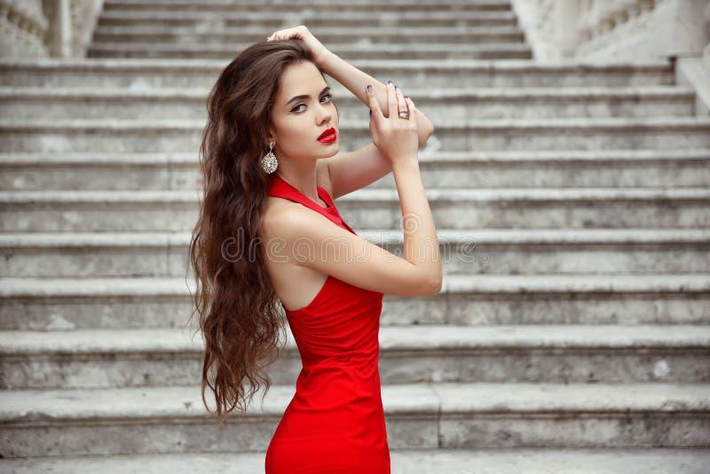 Красивая девушка брюнет в красном платье с длинным здоровым posi волос стоковая фотография