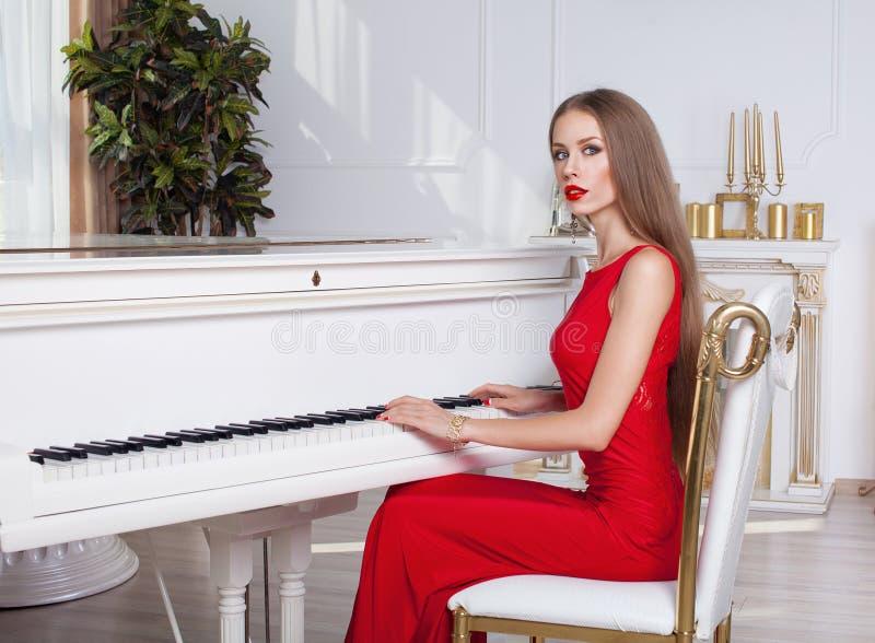 Красивая девушка брюнет в модном платье вечера губы красные красивейшие детеныши женщины студии съемки танцы пар стоковые изображения