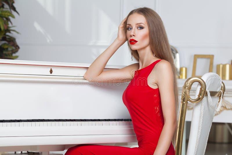 Красивая девушка брюнет в модном платье вечера губы красные красивейшие детеныши женщины студии съемки танцы пар стоковое изображение
