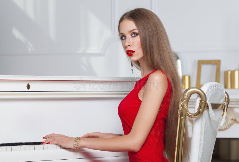 Красивая девушка брюнет в модном платье вечера губы красные красивейшие детеныши женщины студии съемки танцы пар стоковое фото rf