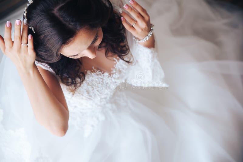 Красивая девушка брюнет невесты в белом платье свадьбы с стилем причёсок и ярким составом стоковые изображения