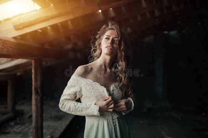 Красивая девушка внутри в белом винтажном платье при вьющиеся волосы представляя на чердаке женщина платья ретро Потревоженная чу стоковая фотография