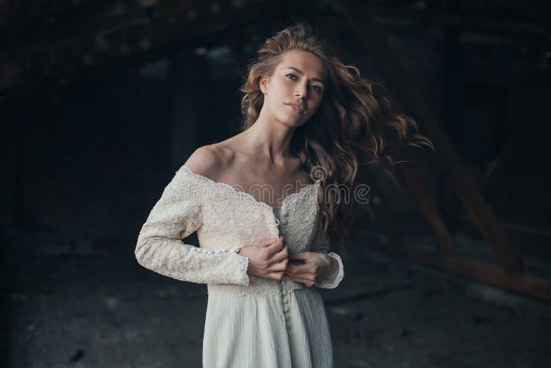Красивая девушка внутри в белом винтажном платье при вьющиеся волосы представляя на чердаке женщина платья ретро Потревоженная чу стоковое фото rf