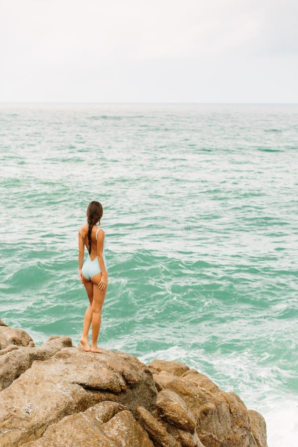 Красивая девушка в голубой прогулке купальника на большом камне стоковое фото