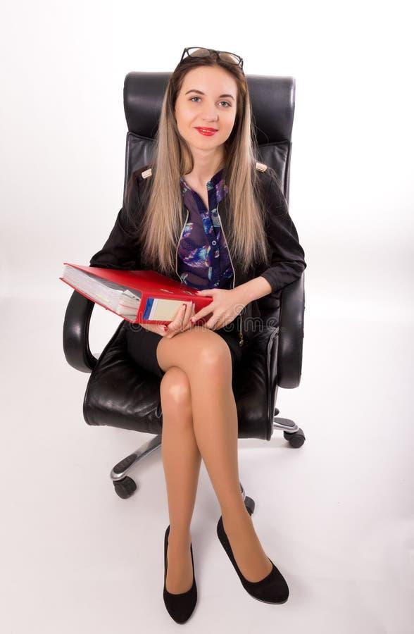 Красивая девушка в деловом костюме сидя в a стоковое фото