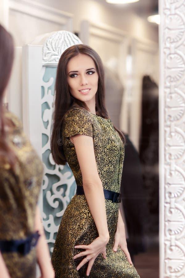 Красивая девушка в золотом платье парчи смотря в зеркале стоковая фотография rf