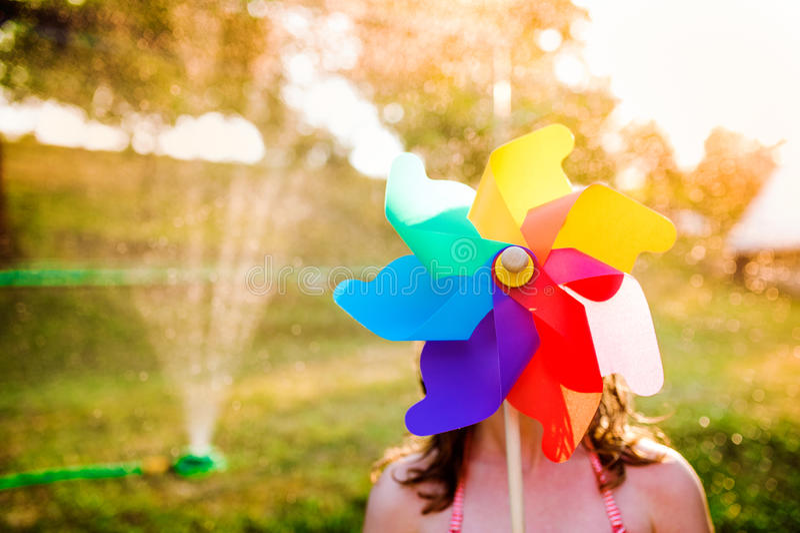 Красивая девушка в купальнике пряча за pinwheel, садом лета стоковая фотография rf