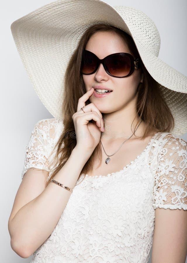 Красивая девушка в обширн-наполненной до краев шляпе представляя и выражает различные эмоции головная боль, тоскливость, усталост стоковое изображение rf