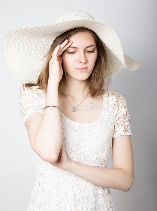 Красивая девушка в обширн-наполненной до краев шляпе представляя и выражает различные эмоции головная боль, тоскливость, усталост стоковые изображения