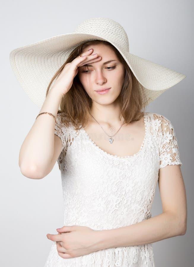 Красивая девушка в обширн-наполненной до краев шляпе представляя и выражает различные эмоции головная боль, тоскливость, усталост стоковые фотографии rf