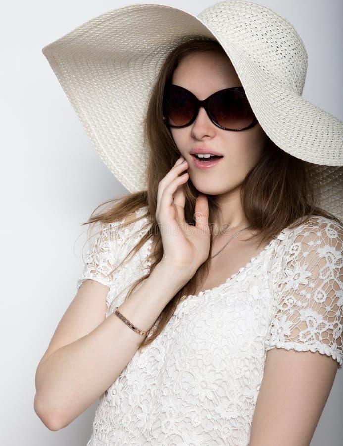 Красивая девушка в обширн-наполненной до краев шляпе представляя и выражает различные эмоции головная боль, тоскливость, усталост стоковое изображение