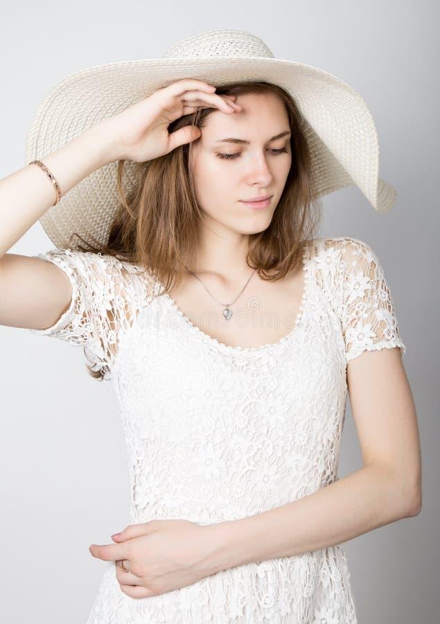 Красивая девушка в обширн-наполненной до краев шляпе представляя и выражает различные эмоции головная боль, тоскливость, усталост стоковые фото