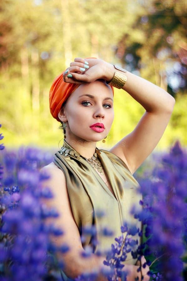 Красивая девушка в поле lupine стоковое изображение rf
